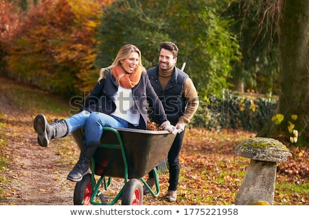 Couple With Wheelbarrow Working Outdoors In Garden stock photo © monkey_business