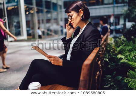 Young elegant banker or lawyer with smartphone sitting in office Stock photo © pressmaster