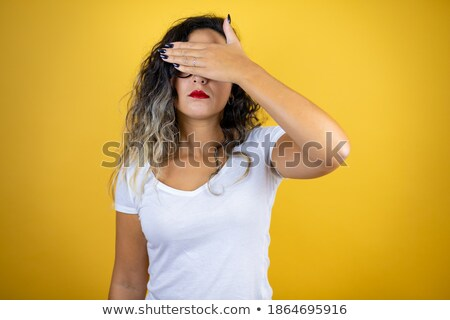 Young brunette female in yellow t-shirt covering her eyes with hands Stock photo © pressmaster