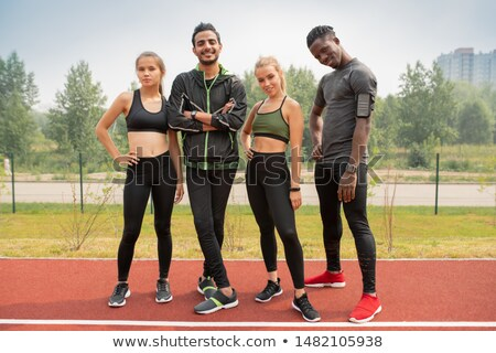 Row of happy young intercultural friends in activewear looking at you Stock photo © pressmaster