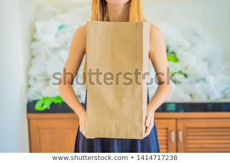 Man holding paper bag amid a pile of plastic bags. Zero waste concept. The concept of World Environm Stock photo © galitskaya