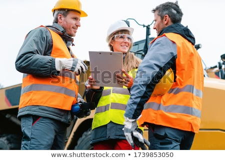 Three workers in a quarry discussing in front of heavy machinery Stock photo © Kzenon