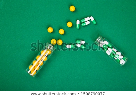 flat lay overhead of yellow and green pills in glass jar on paper background stock photo © illia