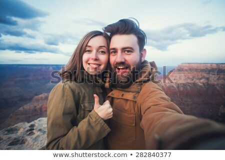 couple taking selfie by smartphone on grand canyon Stock photo © dolgachov