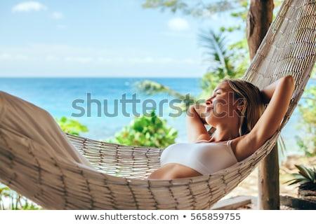 Fiatal nő megnyugtató tengerpart napos idő nő fű Stock fotó © wavebreak_media
