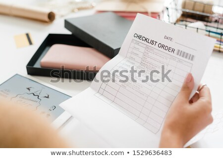Paper with checklist order held by young female shopper looking through it Stock photo © pressmaster