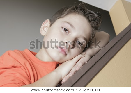 A sad child on the side of staircase. Stock photo © Lopolo