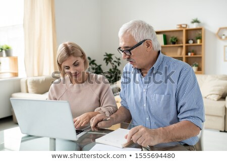 Pretty young woman with laptop and her retired senior father searching for data Stock photo © pressmaster