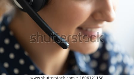 Pretty customer support representative with headset speaking to clients online Stock photo © pressmaster