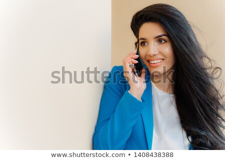 Photo of brunette woman with pleasant appearance, luxurious hair, talks on mobile phone, dressed in  Stock photo © vkstudio