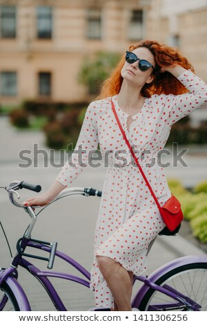 Healthy outdoor activity concept. Lovely curly red haired woman with dreamy expression, uses bicycle Stock photo © vkstudio