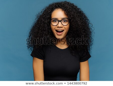 Pleasantly surprised dark skinned woman keeps jaw dropped, gazes with interest, has curly hair, wear Stock photo © vkstudio