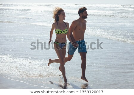 Side view of happy young Caucasian couple holding hands and running by the ocean at beach. They are  Stock photo © wavebreak_media
