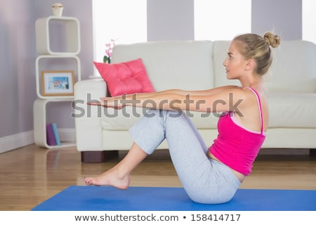 pretty blond haired woman doing fitness exercises in the living room stock photo © wavebreak_media