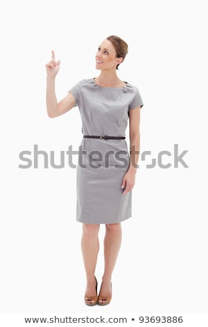 Smiling woman in dress showing something above with her hand against white background Stock photo © wavebreak_media