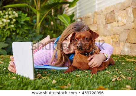 kid girl and puppy dog at homework lying in lawn stock photo © lunamarina
