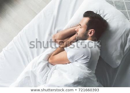 Fiatalember alszik ágy közelkép ház kezek Stock fotó © nito