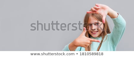 Smiling woman showing framing hand gesture over gray background Stock photo © deandrobot