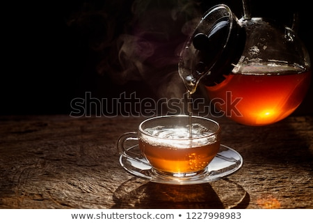 Water being poured into a tea cup stock photo © jrstock