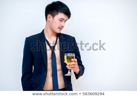 Businessman in black sunglasses holding and looking at beer bottle Stock photo © deandrobot