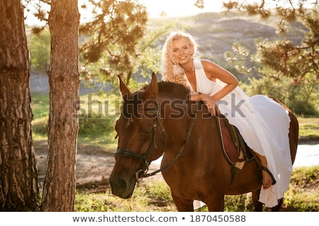 Pretty blond woman posing with a stallion Stock photo © konradbak