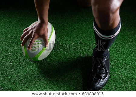 Low section of player standing by rugby ball on playing field Stock photo © wavebreak_media