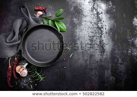 Stock photo: cast iron pan and spices on black metal culinary background, view from above