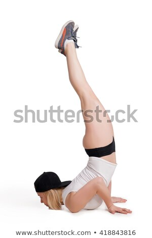 Pretty young woman wearing tank top and briefs standing on hands isolated Stock photo © julenochek