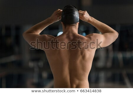 Rear view of a male swimmer adjusting his goggles Stock photo © deandrobot
