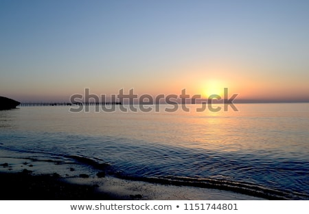 Sun rising above ocean water Stock photo © dash