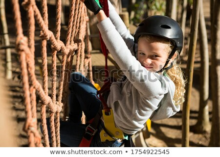 Little girl wearing helmet climbing on rope fence Stock photo © wavebreak_media