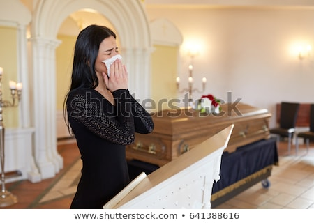 close up of woman with wipe at funeral in church stock photo © dolgachov