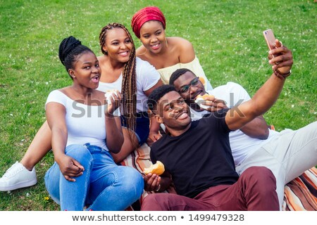 young women friends outdoors in park having fun looking camera take a selfie stock photo © deandrobot