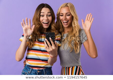 Two pretty excited young girls friends standing Stock photo © deandrobot