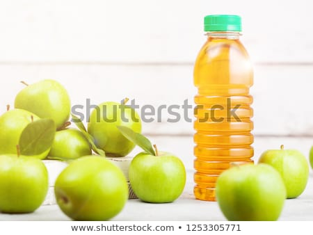 Bottle of fresh organic apple juice with green apples in box on wooden background with sun light stock photo © DenisMArt