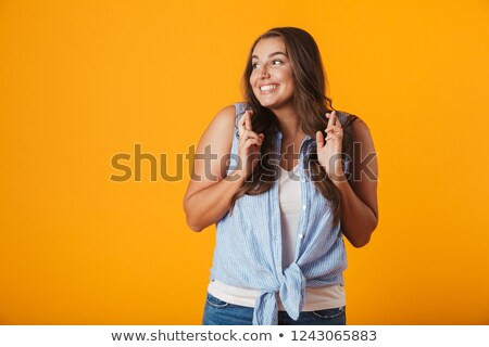 happy young woman posing isolated over yellow wall background showing hopeful gesture stock photo © deandrobot