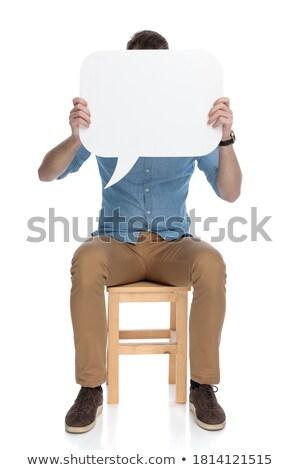 ülő lezser férfi tart szövegbuborék arc Stock fotó © feedough