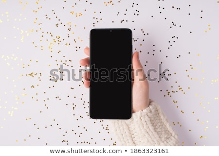 Beautiful girl holds up a shimmering phone. Stock photo © sgursozlu