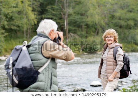 Mature active backpacker photographing his happy wife on river bank Stock photo © pressmaster