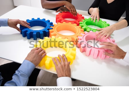 Businesspeople Arranging Colorful Cog Wheels Together Stock photo © AndreyPopov