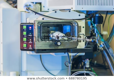 Scientist in a laboratory works with an electron microscope gateway. Putting a sample into a microsc Stock photo © galitskaya