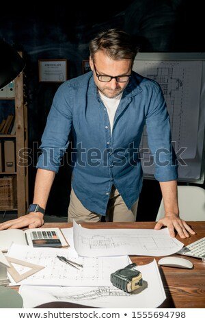 Mature engineer in casualwear looking at sketch on paper while working overtime Stock photo © pressmaster