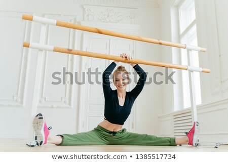 Talented female ballet dancer does splits, holds hands on hadrail, has flexible slim body, practices Stock photo © vkstudio