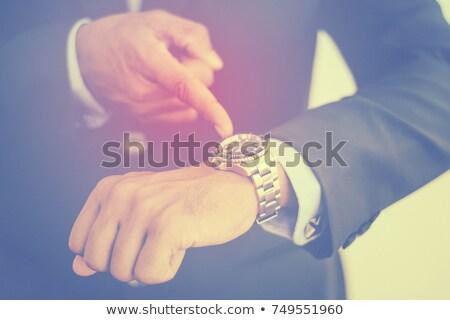 senior businessman checking time on his wristwatch Stock photo © dolgachov