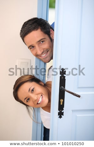 Young couple poking their heads around the front door Stock photo © photography33