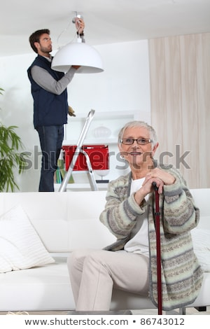 young man fixing lamp for older woman Stock photo © photography33