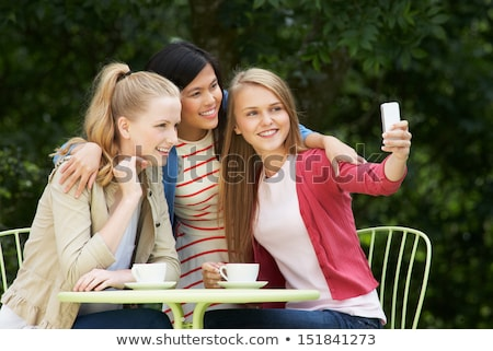 Tinilányok elvesz fotó mobiltelefon szabadtér kávézó Stock fotó © monkey_business