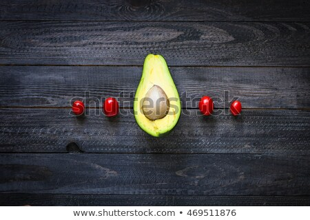 veggie food composition with half avocado over a darkdish stock photo © davidarts