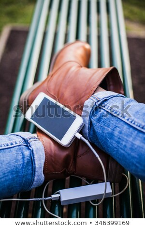 vertical image of woman with power bank and smartphone stock photo © deandrobot