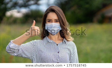 Confident doctor or nurse wearing surgical mask and showing thumbs-up Stock photo © deandrobot